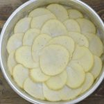 thinly sliced potatoes in round cake pan