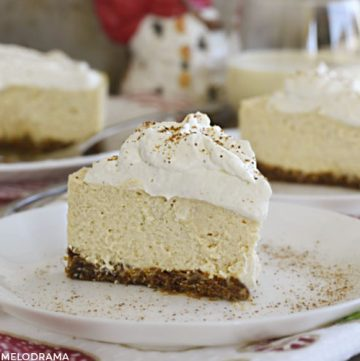 slice of instant pot eggnog cheesecake with eggnog whipped cream on a plate