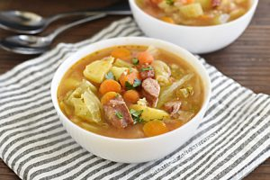 bowl of instant pot kielbasa cabbage soup with potatoes and carrots