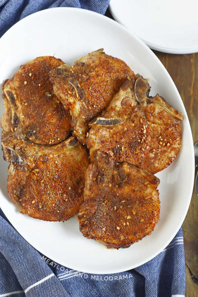 bone-in seasoned air fryer pork chops on white serving tray
