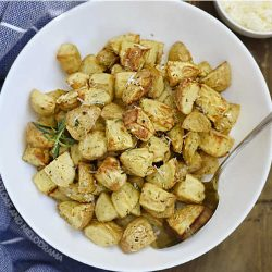 air fryer roasted potatoes with rosemary, garlic and grated Parmesan in a white serving bowl