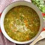 turkey soup with rice, celery and carrots and in a red dutch oven