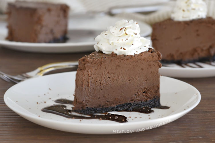 slice of instant pot chocolate cheesecake with whipped cream on a white plate