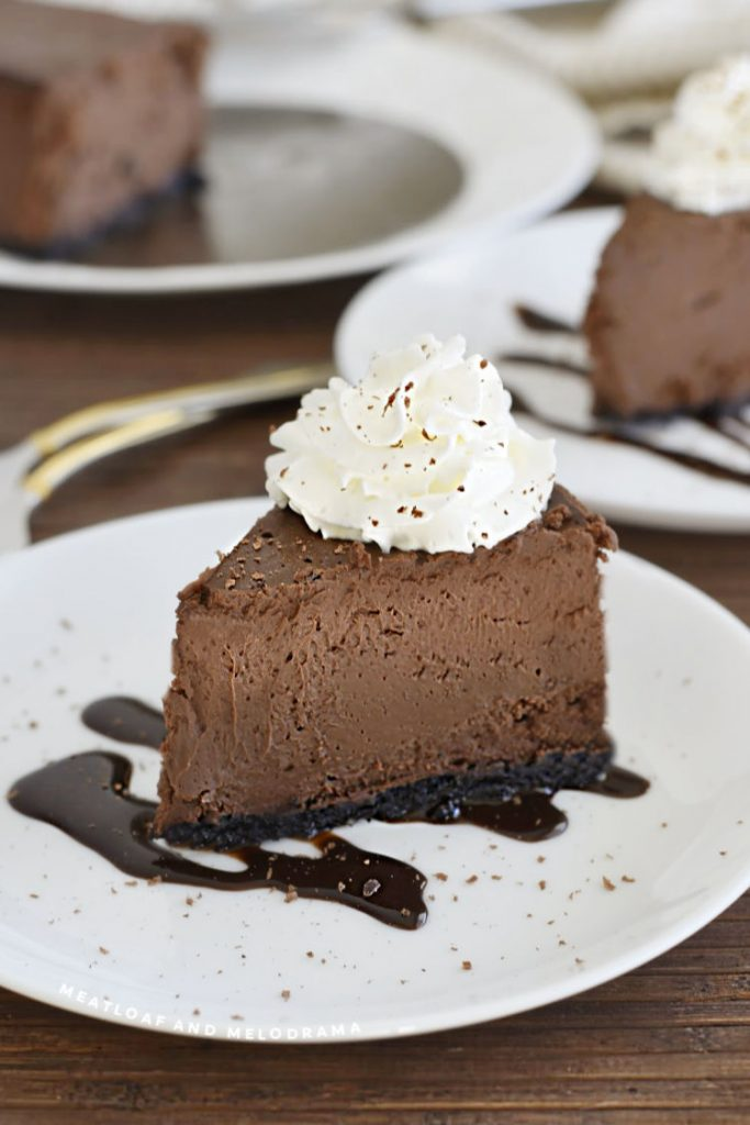 slice of chocolate cheesecake with whipped cream and chocolate shavings