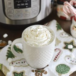 cup of hot chocolate with whipped cream in front of an instant pot