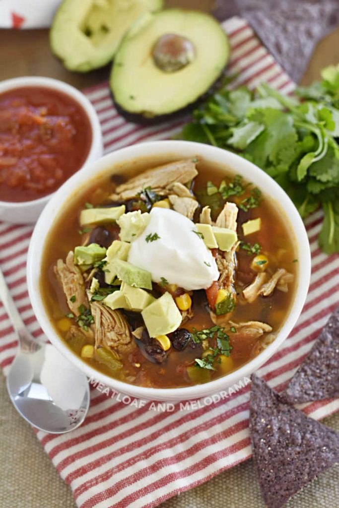 chicken taco soup in white bowl with tortilla chips, salsa, cilantro and avocado in picture