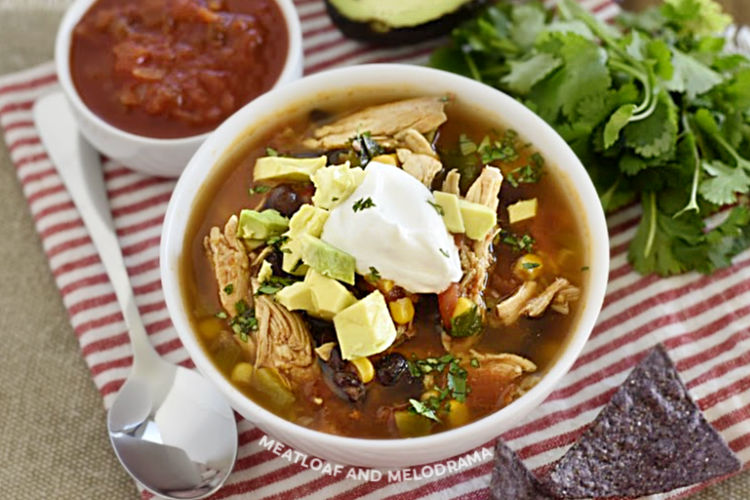 chicken taco soup with black beans and corn topped with sour cream and avocado in a white bowl