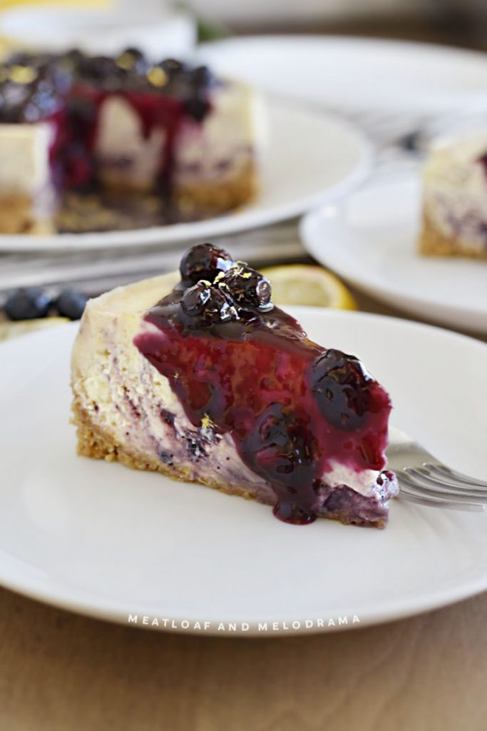 slice of cheesecake with blueberry swirl and blueberry topping on white plate