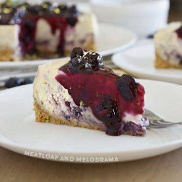 slice of lemon blueberry cheesecake with blueberry sauce on top and sides