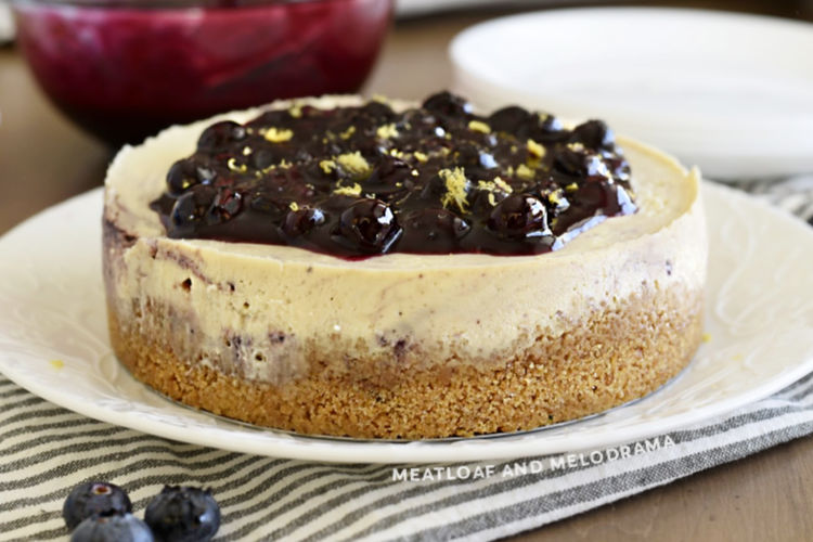 lemon cheesecake topped with homemade blueberry sauce and lemon zest on platter