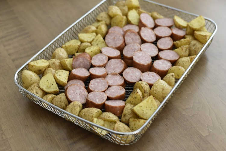 sliced smoked sausage in air fryer basket with potatoes