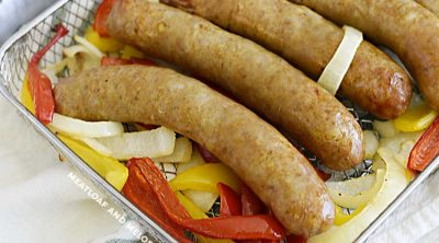 Italian sausages cooked with red and yellow bell peppers and onions in air fryer oven tray