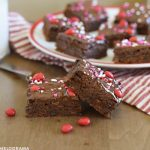 ancho chili brownies with cinnamon imperial candy topping on a red and white plate