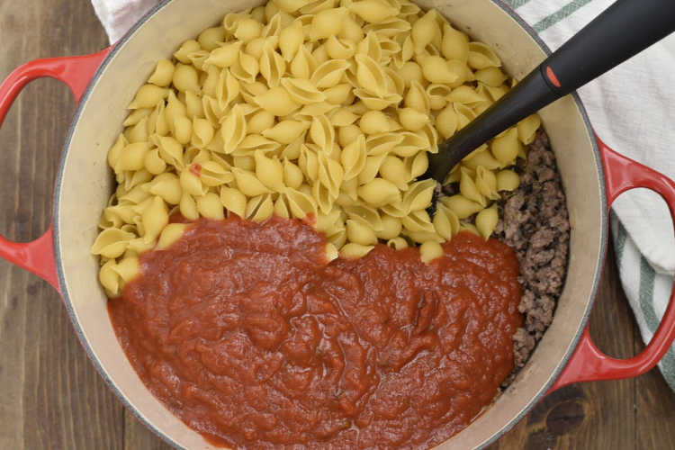 marinara sauce with shell pasta and ground beef in dutch oven