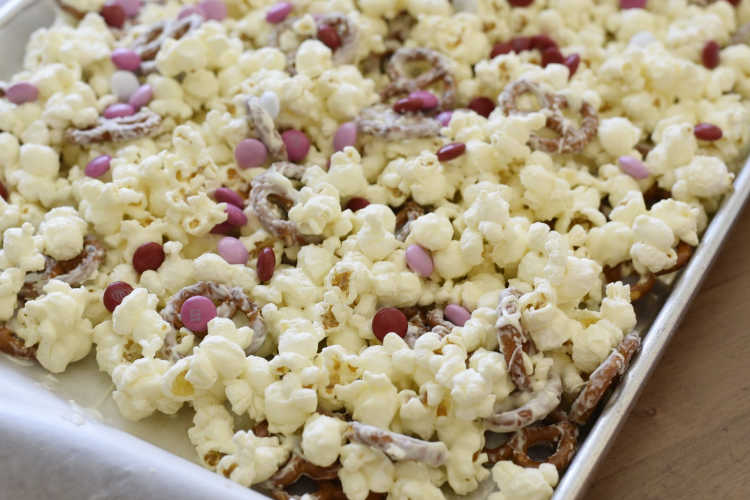 popcorn with pretzels, white chocolate and pink m and m candies on a baking sheet