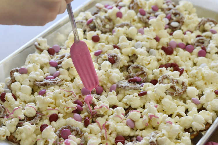 drizzle pink candy coating over popcorn