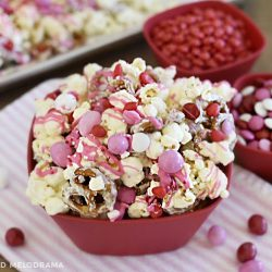 valentines day popcorn snack with red, pink and white candy in a red bowl