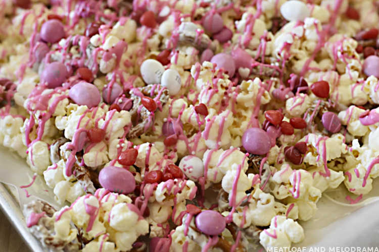 popcorn with valentine's candies and pink candy coating on a baking sheet
