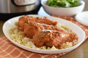 apricot chicken breasts over rice on a white platter