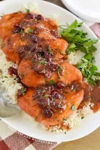 chicken breasts with cranberry sauce on a platter