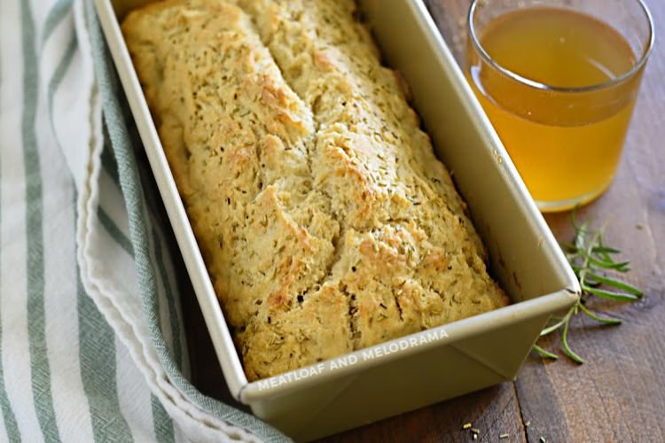 rosemary beer bread in loaf pan with glass of beer