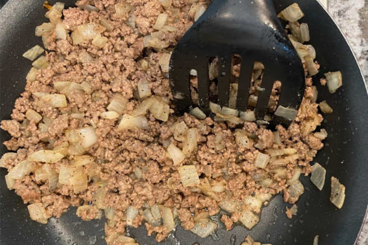 saute ground beef and onions in a skillet