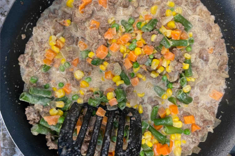 hamburger meat and mixed vegetables in skillet with cream
