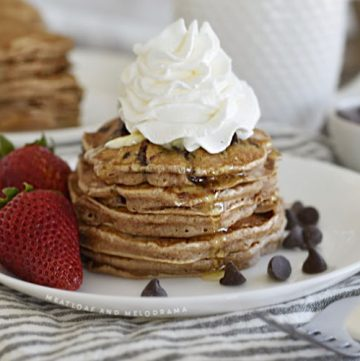chocolate chip pancakes with whipped cream and strawberries on white plate