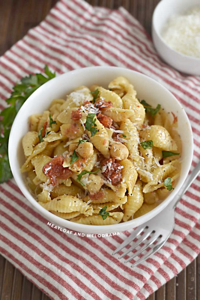 bowl of shell pasta with chickpeas and diced tomatoes with parsley and parmesan
