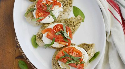 caprese chicken with mozzarella, tomato slices and basil leaves on a platter