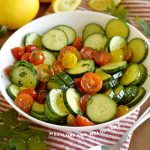 cucumber tomato salad in a white serving bowl