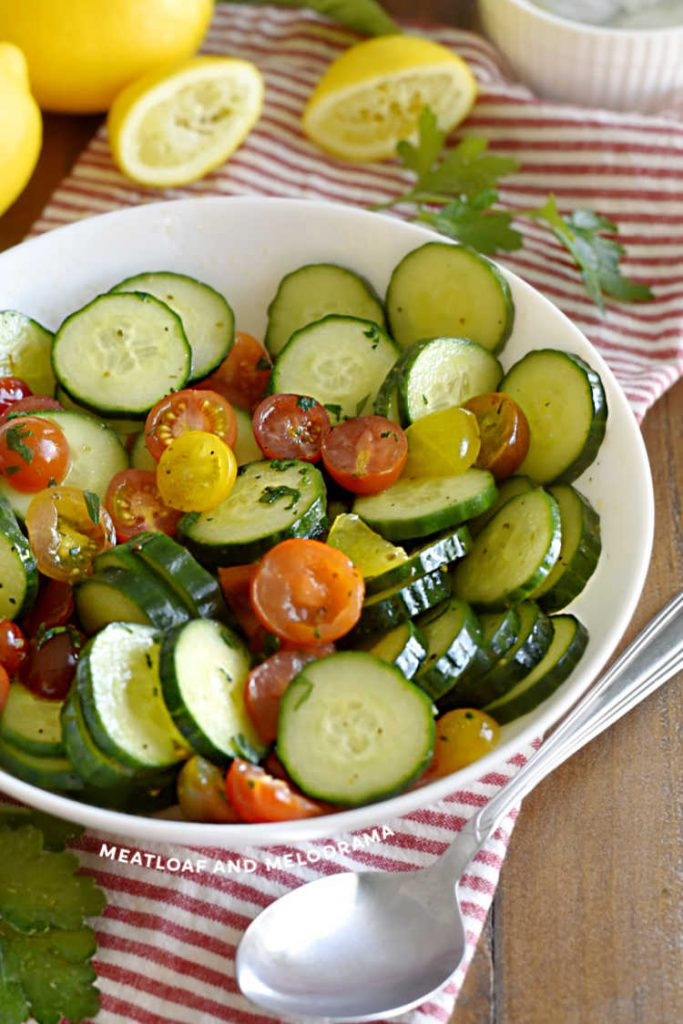 sliced english cucumbers and grape tomatoes in white bowl