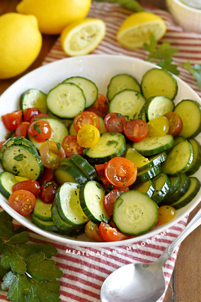 sliced cucumbers and grape tomatoes in a serving bowl with lemon slices