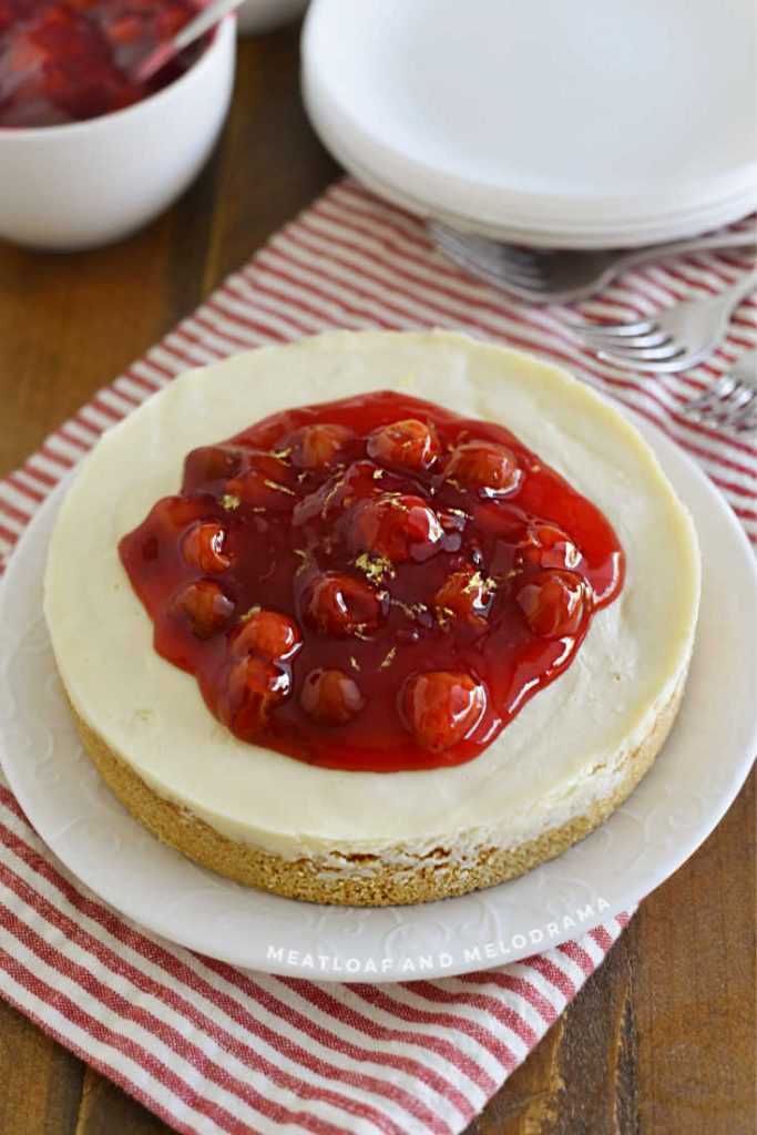 vanilla cheesecake topped with cherry pie filling on a white plate