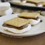 s'mores with graham cracker, marshmallow and melted chocolate on a white plate