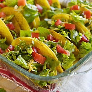 oven baked tacos with lettuce and tomatoes in a glass baking dish
