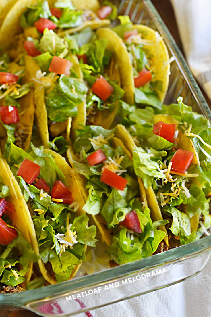 baked tacos with lettuce and tomatoes in a glass dish