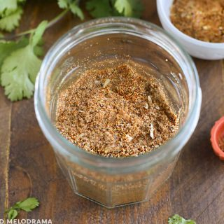 jar of homemade taco seasoning on wood board with cilantro