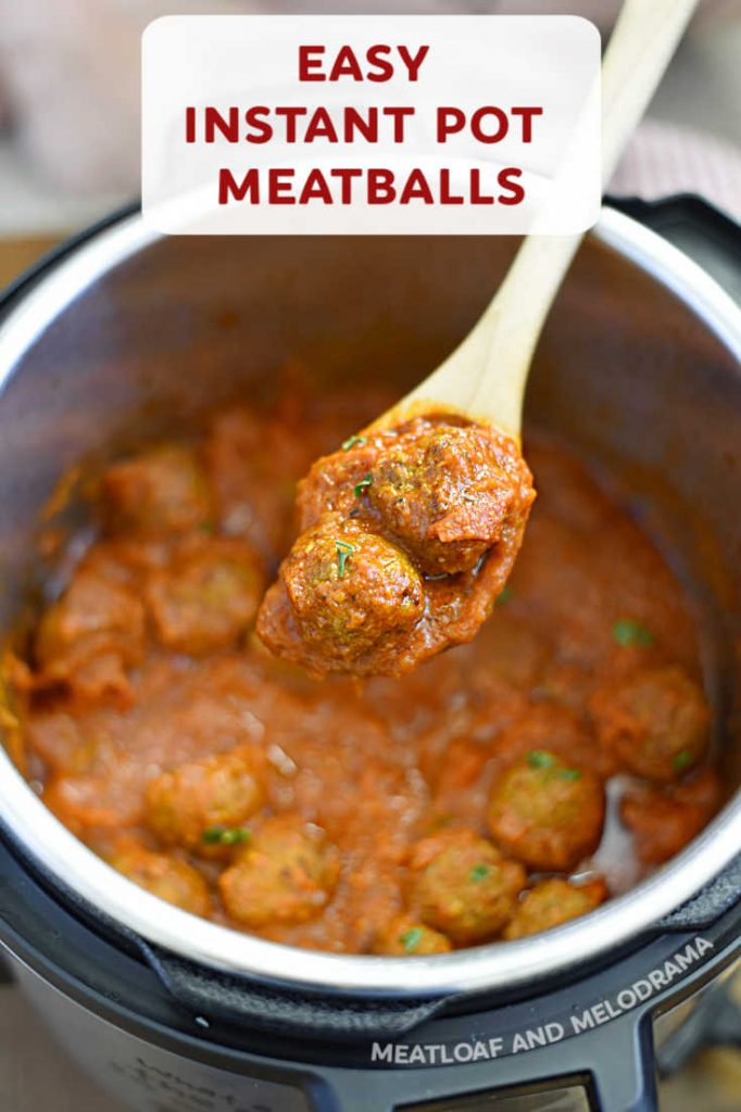 close up of meatballs in marinara sauce on wooden spoon
