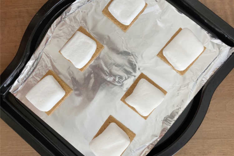 graham cracker halves with marshmallows on top on baking sheet