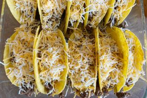 shredded cheese over beef in taco shells
