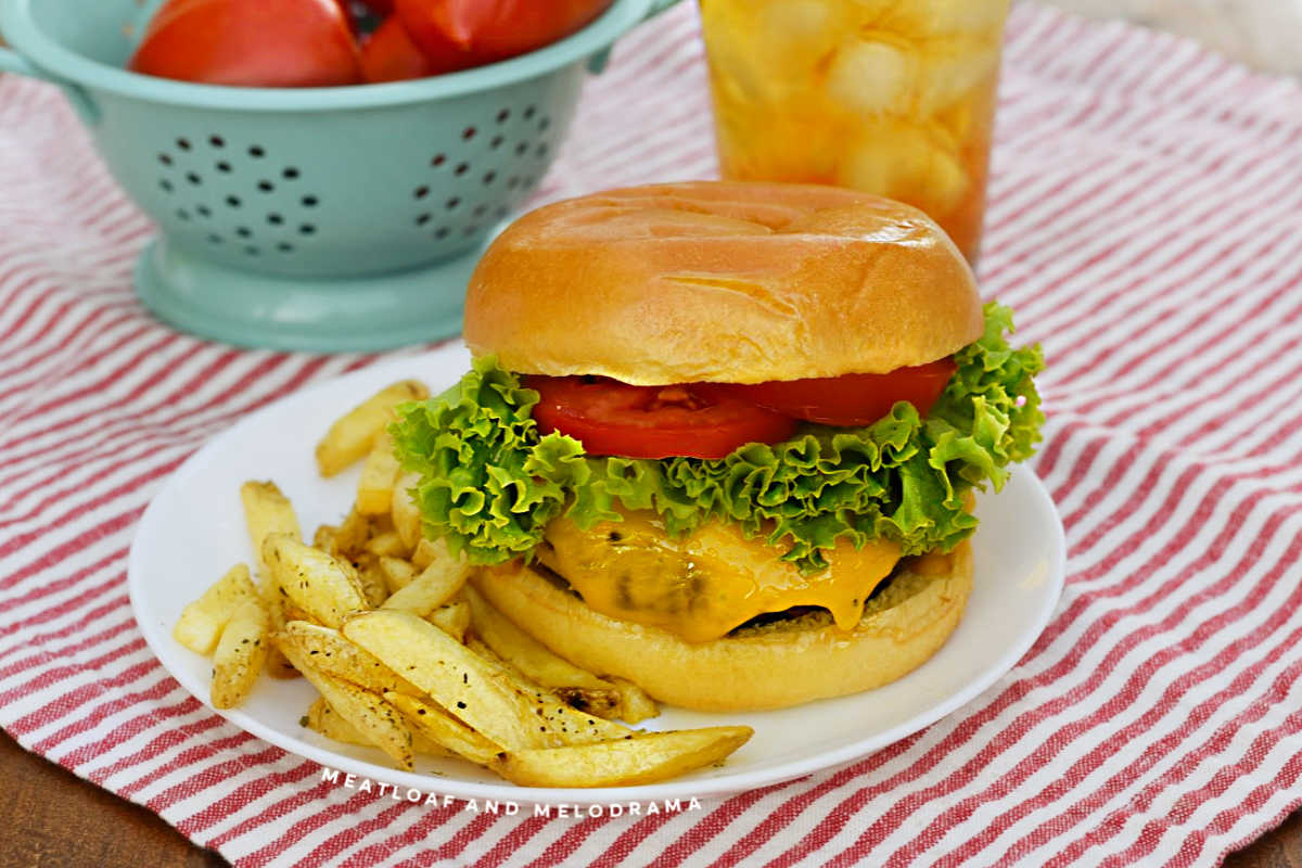 air fryer hamburger with melted cheese, lettuce and tomato slices on a plate with fries