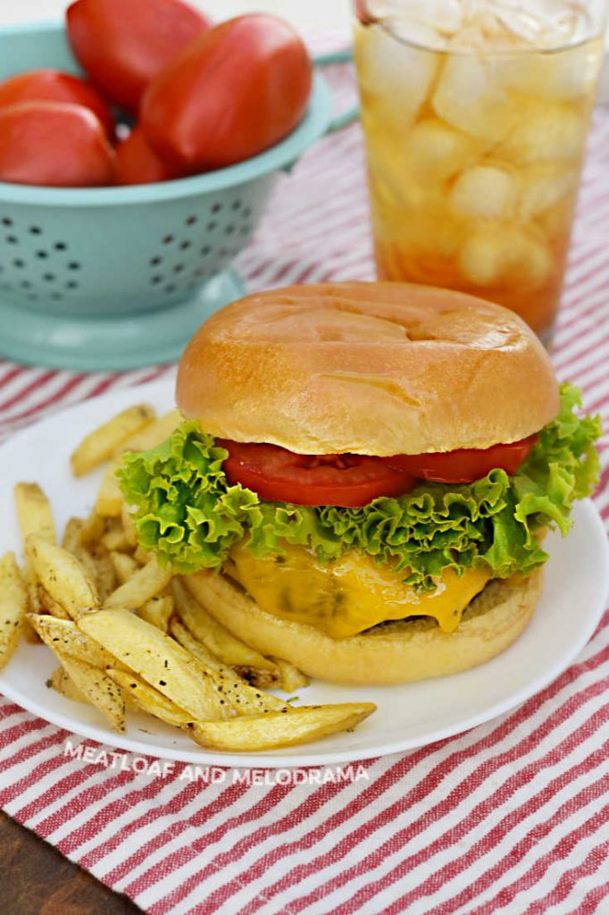 cheeseburger with lettuce and tomato on plate with fries