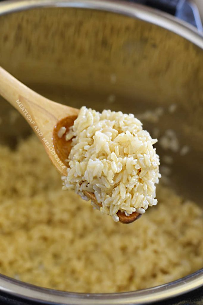 perfectly cooked brown rice on wooden spoon over instant pot