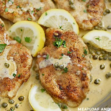 chicken piccata in cream sauce with lemon slices in a skillet