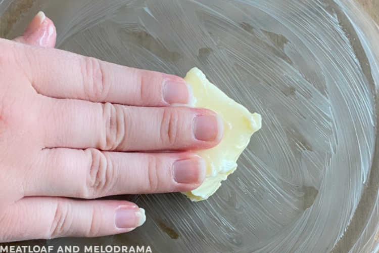 hand spreading butter on a glass pie pan