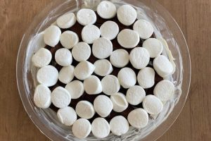 marshmallows over chocolate bars in glass pan
