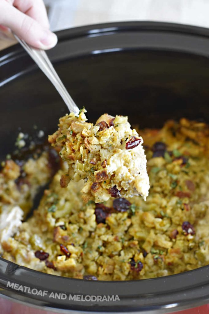 chicken and stuffing on serving spoon over slow cooker