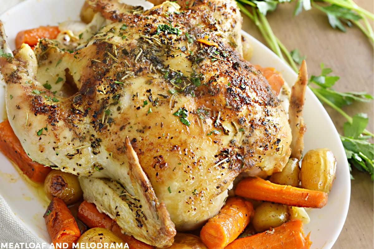 roast chicken with carrots and potatoes on a platter with parsley