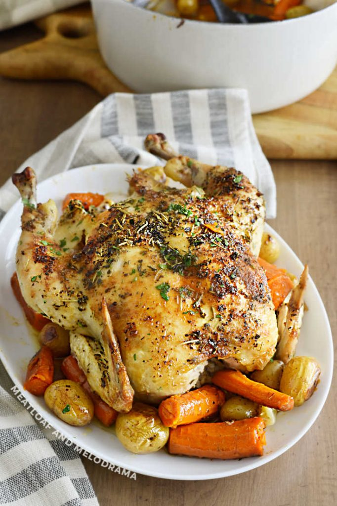 roast chicken over carrots and potatoes on a white platter